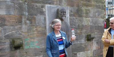 Vor der Behring-Büste und dem ehemaligen Hygieneinstitut in Marburg erläutert Historikerin Julia Langenberg wie Emil von Behring sich kommunalpolitisch auch für sauberes Trinkwasser einsetzte. (Bild: m_)