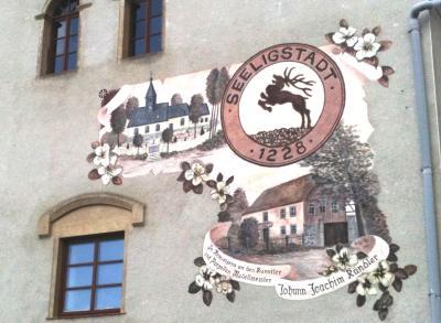 Wandbild mit dem Wappen Seeligstadt 1228 und Gedenken an den Porzellangestalter Kändler